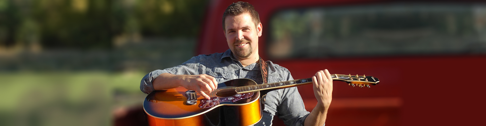 Nathan Osmond playing guitar with blurred truck in background