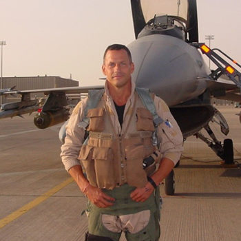 Colonel Dan Hampton hands on hips in front of airforce jet
