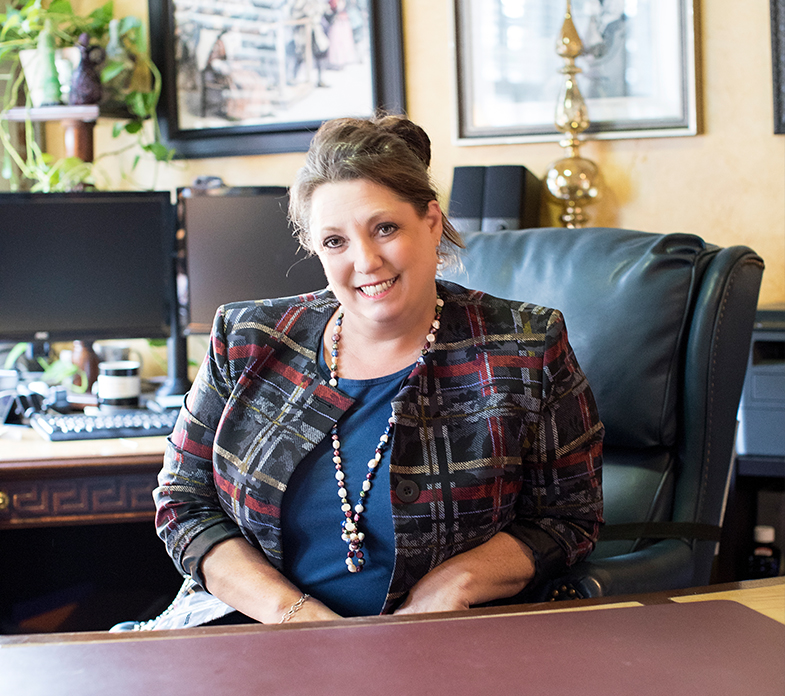 Julie Ketterman sitting at desk in her office